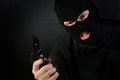 Terrorist in a ski mask holding a gun with a dark background Stock Photo