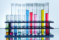 Test tube rack with chemical tubes with colored fluid in laboratory blue background Royalty Free Stock Photos