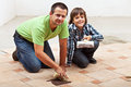 Testing the color of joint on ceramic floor tiling father and son Royalty Free Stock Photos