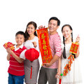 Tet celebration portrait of a cheerful family with ornaments posing at camera over white Royalty Free Stock Photo