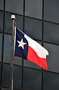 Texas flag a state is blewing in the wind outside a office building in downtown tyler Royalty Free Stock Images