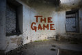 Text the game on the dirty old wall in an abandoned  house Royalty Free Stock Photo