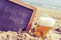 Text goodbye summer in a chalkboard and a glass of beer on the b Royalty Free Stock Photo