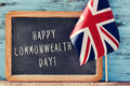 Text happy commonwealth day a chalkboard with the written in it and the union flag on a wooden surface against a blue rustic Stock Photography