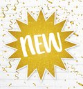 Text label new in golden glitter star with confetti on backgroun Royalty Free Stock Photo