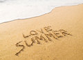 Text love summer written in the sand on the beach with a wave Royalty Free Stock Images