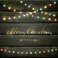 Colorful Christmas lights on black wooden background