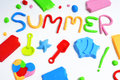 Text summer made from modelling clay the of different colors and some beach toys such as toy shovels and sand moulds on a white Stock Photos