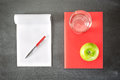 Textbook an a notebook open with blank pages next to red book or photographed from above Stock Photography