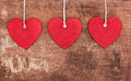 Textile pendent hearts on old shabby wooden background Royalty Free Stock Photo
