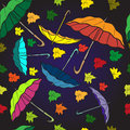 Textile seamless pattern of colorful umbrellas and autumn leaves
