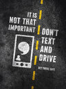 Texting and driving warning about the dangers of over concrete background Royalty Free Stock Images