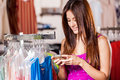 Texting a friend and shopping pretty latin woman sending text to while doing some in clothing store Royalty Free Stock Image
