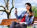 Texting with her smartphone photo of a beautiful young woman using a while sitting on a park bench Royalty Free Stock Photo