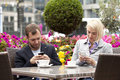 Texting young couple having coffee in street cafe busy with their mobiles Stock Photo