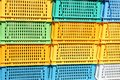 Texture from colored plastic colored yellow blue green rectangular boxes with holes for goods, bottles Royalty Free Stock Photo