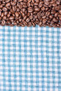 Texture of a colored towel, a towel of a cellular type, on which lies a certain amount of brown coffee beans. Top view with a bunc