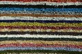 Texture of fluffy handmade carpet produced on hand-loom, pattern of various colorful vertical lines