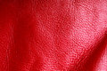 Texture of folds vivid red skin leather background closeup wavy natural material Stock Photography