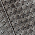 Texture of genuine dark wicker leather close-up and details with stitches of male handbag. Concept of shopping
