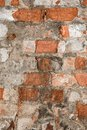 Texture of an old wall of an ancient building with a ruined plaster layer and cracked red bricks