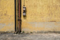 Texture of old yellow vintage wall of industrial factory with rusted iron pole and electric cable