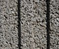 Texture of a wall of small, small gray stones with two dimples in the middle
