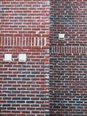 stock image of  Textured brick wall with utility panels present.