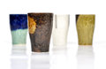 Textured coffee mugs a brownish mug with three others in the blurred background Stock Photography