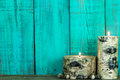 Textured log candles burning by antique green background Royalty Free Stock Photo