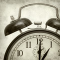 Textured old paper background with fashioned alarm clock Royalty Free Stock Photography