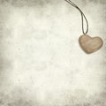 Textured old paper background with wooden heart pendant Royalty Free Stock Photos