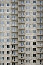 Textured pattern of a russian whitestone residential house building wall with many windows and balcony under constructio Royalty Free Stock Photo