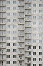 Textured pattern of a russian whitestone residential house building wall with many windows and balcony under construction Royalty Free Stock Photo