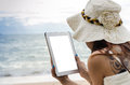 On th beach young woman using tablet against background Royalty Free Stock Photos