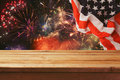 4th of July background. Wooden table over fireworks and USA flag. Independence day celebration Royalty Free Stock Photo