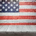 4th of july background with wooden table over USA flag painted on brick wall Royalty Free Stock Photo