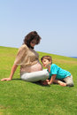 Th pregnant woman rests with four year old son charming young women lovely on the grass near the sea Royalty Free Stock Photos
