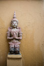 Thai angel sculpture on brown concrete wall Royalty Free Stock Images