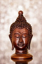 Thai buddha head a wooden on a blurry sparkling background Royalty Free Stock Image