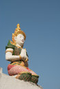 Thai fairy sculpture sit on the pagoda below a blue sky Stock Image