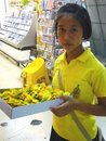 Thai girl selling yellow flowers Royalty Free Stock Photography