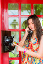 Thai girl is talking with an old fashion phone in the telephone booth Royalty Free Stock Photos