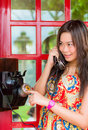 Thai girl is talking with an old fashion phone in the telephone booth Stock Photo