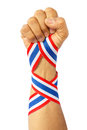Thai man fist and bind thai flag pattern ribbon on forearm Stock Photo