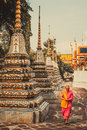 Thai monk is walking in front of old ancient pagoda at Wat Pho Temple in Bankgok, Thailand.