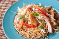 Thai noodles with shredded chicken a peanut infused noodle dish red peppers green onions sit on a blue plate Stock Photos
