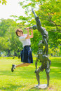 Thai schoolgirl is jumping with statue in park cute a the Stock Images