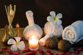 Thai spa massage setting on candlelight with towel frangipani herbal compress balls candle aroma reed diffuser and rose petals Royalty Free Stock Photography