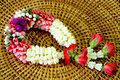 Thai style garland beautiful fresh flower on woven wood background Royalty Free Stock Image